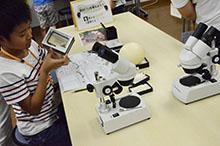 恐竜の卵化石を手に持つ男の子と実体顕微鏡